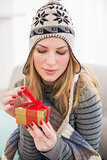 Pretty woman sitting on a couch while opening a gift box