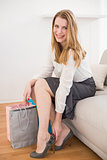 Smiling woman sitting on couch taking off her shoes