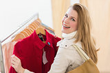 Smiling blonde picking out jacket