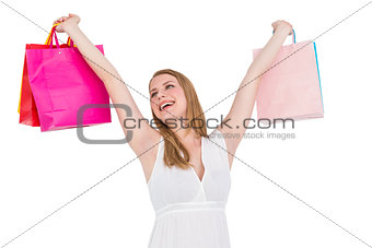 Blonde woman raising shopping bags