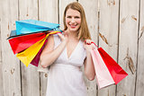 Smiling woman carrying shopping bags over her shoulder
