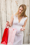 Elegant blonde woman opening a gift bag