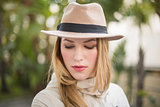Pretty blonde woman with hat posing while looking down