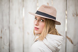 Pretty blonde woman with hat looking over her shoulder