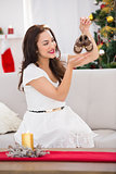 Happy brunette holding baby shoes at christmas
