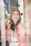 Smiling brunette in christmas hat holding mug