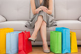 Elegant woman sitting on the couch with shopping bags