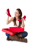 Content brunette holding red shoes