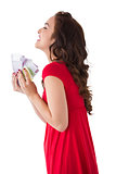 Happy brunette in red dress holding cash