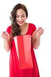 Stylish brunette in red dress opening gift bag