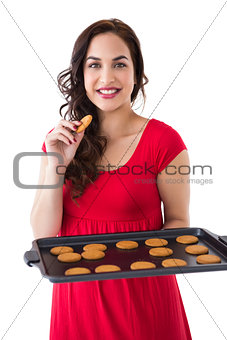 Smiling blonde eating hot cookies