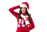 Stressed brunette in santa hat holding gifts