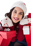 Happy brunette holding shopping bags full of gifts