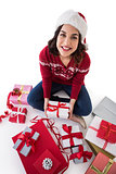 Happy brunette sitting and wrapping christmas presents