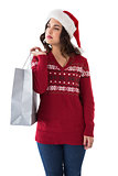 Thoughful brunette in santa hat holding shopping bag