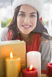 Portrait of pretty brunette behind candles