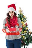 Festive brunette holding gift by the tree
