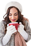Brunette in winter clothes holding a mug