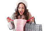 Surprised brunette looking in shopping bag