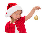 Cute little girl wearing santa hat holding bauble