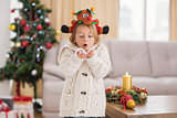 Festive little girl blowing over hands