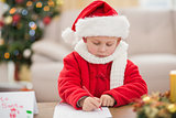 Festive little boy writing wish list
