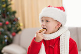 Festive little boy eating a cookie