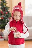 Festive little boy dipping cookie in milk