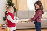 Festive siblings pulling a cracker