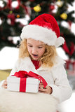 Festive little girl looking at gift