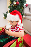 Cute boy in large christmas present drinking milk