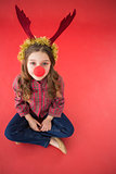 Festive little girl wearing red nose