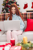 Festive redhead using laptop on couch