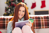 Festive redhead shopping online with tablet
