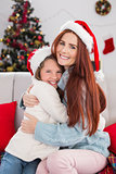 Festive mother and daughter hugging on the couch