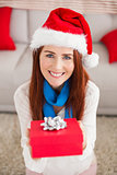 Festive redhead smiling at camera holding gift