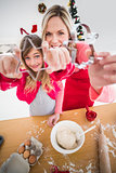 Festive mother and daughter making christmas cookies