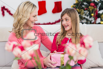 Little girl giving her mother a christmas gift