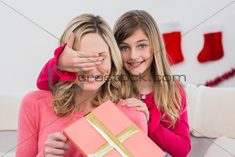 Little girl hiding gift from mother