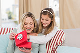 Mother opening christmas gift with daughter