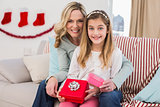Daughter opening christmas gift with mother