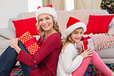 Festive mother and daughter smiling at camera with gifts