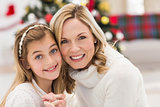 Festive mother and daughter beside christmas tree