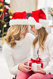 Festive mother and daughter smiling at each other