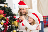 Festive mother and daughter decorating christmas tree