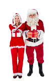 Santa and Mrs Claus smiling at camera offering gift