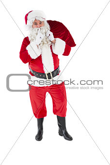 Santa holding sack and keeping a secret