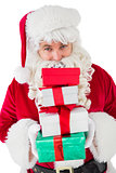 Smiling santa holding pile of gifts