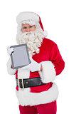 Happy santa showing digital tablet