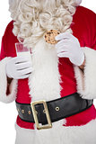 Santa holding glass of milk and cookie